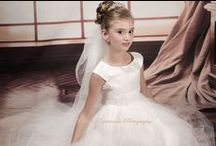 First Communion Dress of the Day Style D1184 / First Communion Dress of the Day! Pretty tea length first communion dress or flower girl dress. Made of polyester/acetate. This dress is made in the USA and is satin with organza overlay. Rhinestone beading around waist. Satin tie back.