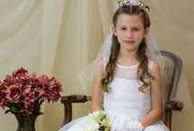 First Communion Dress Style 8013 /  Beautiful First Communion Dress with Satin skirt with organza overlay. Bodice has organza layers with sheer neckline with floral beading. Waistline has pretty organza flower. Tea length. Zipper closure