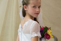 First Communion Dress Style 6833 / Satin first holy communion dress with organza overlay accented with lace throughout and satin banding. V-neck back. Tea length with short sleeves. Lace trimmed scallop hem. Zipper closure in back. Fully lined. Available exclusively at Christian Expressions