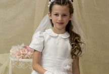 Embroidered Organza First Communion Dress Style 6830 / Gorgeous short sleeve tea length first holy communion dress with peter pan collar. Satin with organza overlay with allover embroidery flowers accented with pearls and sequins. Organza cumberbun with organza bow at waist. Zipper closure in back. Fully lined