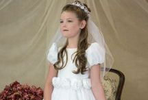 Long Length FIrst Communion Dress Style 6308 / First Holy Communion Dress with Short puf sleeves and bateau neckline highlight satin bodice. Five satin roses adorn the waistline. New tulle skirt trimmed with satin at hemline.