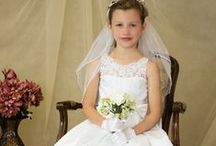 Tea Length First Communion Dress with Lace Bodice Style 8022 / Sleeveless, lace bodice first communion dress with pleated satin skirt and satin bow accent in tea length. Zipper back. Order early to ensure your child has her special first communion dress This is new for first communion season 2015 - 2016  and is sure to sell exclusively through Christian