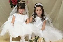 Satin and Tulle Beaded First Communion Dress D1102 / Pretty tea length first communion dress or flower girl dress. Made of polyester/acetate. This dress is made in the USA and is satin with organza overlay. Pearl accents throughout. Satin tie back