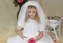 First Communion Dress Style 8010 / First Communion Dress with Satin skirt with tulle overlay . Bodice has zig zag design accented floral pattern with double flowers at waist. Tea length. Zipper closure with tie bow in back.  http://www.firstcommunions.com/