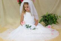 Pleated Skirt First Communion Dress Style 6803 / Pleated Tea Length First Communion Dress Style 6803 (12 photos) Sleeveless first holy communion dress made of satin top with embroidered 'leaves' design with large flower with rhinestone center and pleated organza overlay skirt. Fully lined. Tea length. Available exclusively at Christian Expressions