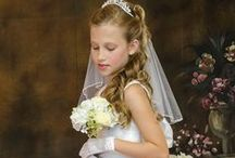 First Communion Dress Style Zoe / Sleeveless Floral jacquard first communion dress with daisy pattern. A line style with pleated skirt. Zipper closure with satin cumberbun and satin bow tie back. Fully lined .  Tea length. Made in the USA.   This first communion dress is available in plus size. New for season 2016