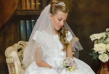 First Communion Dress Style Tabitha / Organza and satin tea length first communion dress with cap sleeves. Pretty floral accents. Zipper closure with bow satin tie. The first communion dress is new for season 2016 and Made in the USA