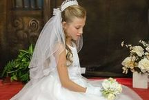 First Communion Dress Style Renee / Organza and satin tea length first communion dress with lace bodice, organza bow with rhinestone accent . Zipper closure with bow satin tie. Fully lined. The first communion dress is new for season 2016 and Made in the USA