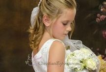 First Communion Dress Style Natasha / Beautiful sleeveless Satin bodice with beaded applique first communion dress. Tulle skirt with satin trim. Pearl trim neckline and ornate bow on back. Zipper closure. Includes a satin shawl. Fully lined .  Tea length. Made in the USA.   This first communion dress is available in plus size.