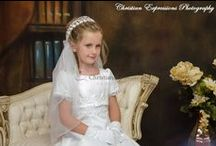 First Communion Dress Style Mary / Short sleeve Satin A line first communion dress with pearls and beading trim along waistline, sleeves, hem. Dainty satin bow along bodice Zipper closure.  Fully lined .  Tea length. Made in the USA.   This first communion dress is available in plus size.  New for season 2016