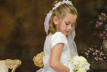 First Communion Dress Style Christina / Short sleeve matte satin tea length first communion dress with eyelet floral design with organza overlay.   Zipper closure with organza bow tie back. Scalloped hem. Fully lined. The first communion dress is new for season 2016 and Made in the USA.