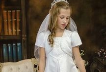 First Communion Dress Style SP703 / A line satin tea length first communion dress with split style skirt in front and back accenting beading details throughout. Matching bolero jacket. Zipper back. The first communion dress is new for season 2016 and Made in the USA