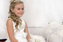 Asymmetrical First Communion Gown / This beautiful asymmetrical layered organza and satin first communion gown features a stylish zig zag tie back with embroidered bodice, satin sash and organza bow on waistline. This dress is available exclusively at Christian Expressions