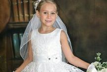 Lace and Sequins First Communion Dress / Sleeveless tea length first communion dress features a full sequined lace overlay skirt with scalloped hemline, pretty lace sequined bodice accented with a satin sash with rhinestone flower on waist . Zipper back with organza tie bow.