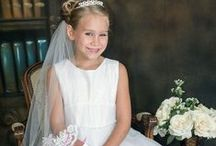 Organza Mesh First Communion Dress / Sleeveless tea length first communion dress features a full sequined double layer tulle skirt with ruffled hemline, mesh bodice with small rhinestone accents along waistline and scattered sequins throughout dress . Zipper back with organza tie bow.