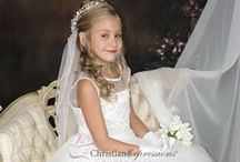 First Communion Dress Beaded Tulle and Satin / Sleeveless tea length first communion dress features a fully lined tulle skirt with sequin appliques, satin bodice with sequins  and pearls and  sheer orgnaza neckline.  Zipper back with organza tie bow.