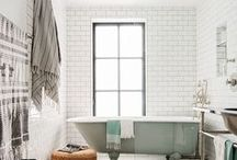 bathroom. / white, bright and tidy. greenery throughout, beautiful tiling. fluffy towels and pops of metal.