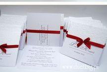 Dodatki białe + bordowy / Białe zaproszenia z bordową taśmą i obowiązkowo uroczą cyrkonią na kokardce. Okładka przyozdobiona białym tłoczonym papierem z motywem kwiatów.