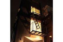 東京組|マンハッタンな家 / 摩天楼を望み、近くを地下鉄が走り、下町を感じる場所。間口が狭く、奥行のある狭小敷地。ニューヨークの古いタウンハウスをリノベしたような住宅を表現。外と内のギャップ。 外観は危ないエリアに立つダウンタウンの古い建物の雰囲気を醸し出すブラック。ファサードに一部レンガを使い、建物の顔となる鉄骨非常階段を設置。屋上は新宿のビル群を眺め、自分だけの空を満喫できる場所。内観は狭さを感じず、差し込む光が眩しいクールなホワイト。 風水を取り入れた間取りとアクセントの色。 インナーバルコニーは明るさを取り込み、フレキシブルで贅沢な空間。内装材は補修のしやすさを考慮、自らがリノベを楽しんでいける住宅。