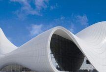 Zaha Hadid / Zaha Hadid (Bagdad, 31 oktober 1950 – Miami, 31 maart 2016) Dame Zaha Hadid, was een Britse architecte van Iraakse afkomst. Ze studeerde wiskunde aan de Amerikaanse universiteit in Beiroet en daarna architectuur aan de AA in Londen. Werkte bij het OMA van Rem Koolhaas. Van een sensueel lijnenspel in haar ontwerpen maakte de architecte haar persoonlijke handtekening. Haar eerste belangrijk uitgevoerd ontwerp in Europa was in 1993 de brandweerkazerne op het fabrieksterrein van Vitra.