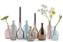 BARLUME - GLASS CANDLE HOLDERS / Barlume is a trio of glass candle holders and vases inspired by the most classic and iconic object of Italian tables and osterias. The stylised bottle comes in a contrast combination of metal finishes and delicate transparent colours, which range from gray to light blue to fuchsia, applied using the ancient luster varnish technique of the Venetian glassmakers. A minimal yet precious decoration for a romantic atmosphere.