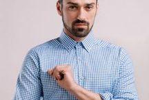 Koszula w biało – niebieską kratkę z kontrastowymi wstawkami / Kołnierz klasyczny zapinany na guziki. Wewnętrzna listwa z guzikami w kolorze szarym. Łaty ozdobne na rękawach.  100% bawełna Twill