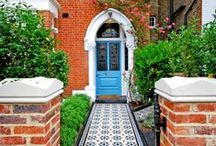Elms Front Garden by Really Nice Gardens / We designed this Clapham front garden with beautiful blue mosaic tiles to match the blue door, creating a stark contrast to the traditional red brick house.
