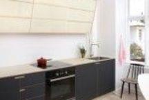 Sct. Thomas Allé / Nicolaj Bo™ greb og skråtskåret overskab  Dette køkken, som bor på Sct. Thomas Allé, er beklædt med koksfarvet linoleum. Grebene er nedfræset i ask og bordpladen er i massiv ask.    Overskabet (80 cm * 230 cm) er i asketræsfinér med skydelåger i tre etager i opal mælkehvid akryl. Slagbænken er lavet i askefinér og og spisebordet, som også er designet specielt til rummet, er i asketræ med lys linoleum.   Pris cirka DKK. 130.000,- inkl. moms og montage.