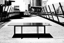 """Jonathan / La collezione del Tavolo """"Jonathan"""" ha come base una struttura metallica tubolare che rimane invariata a differenza dei piani che variano di materiale e fnitura. Questa struttura è costituita da un tubolare metallico di 20x60mm rivestita in vernice epossidica nera lucida. Per i tavoli alti vengono proposti piani in masonite, in lamiera smaltata ed in cristallo. La lamiera smaltata rende il tavolo molto resistente a graffi e usura."""