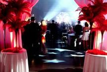Great Gatsby Gala / The venue was divided into two distinct areas to separate the dual themed event. Upon arrival, the guests were greeted to a true Roaring Twenties atmosphere complete with red feather vignettes, silver candelabras draped with white pearls and black feather boas. A swing band played in the background as guests were offered a signature drink.  Once inside, a feeling of prohibition with wooden crates & barrels, old fashioned vignettes and a full casino transported the crowd to the world of Speakeasy