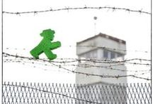 Grenzgänger / Zu Zeiten des Kalten Krieges geboren, lebten die Ampelmännchen lange eingesperrt hinter der Mauer, die Deutschland in zwei Staaten teilte. Erst als diese fiel, wurden sie befreit. Heute posieren sie anlässlich des 25jährigen Mauerfalls für Fotos entlang des ehemaligen Eisernen Vorhangs. Diese Grenze quer durch Europa nennt man heute Grünes Band.