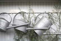 watering cans / The name 'Watering Can' first appeared in 1692 ... Before that, the term 'Watering Pot' was used. Pots had holes in the bottom at first, before the idea of a spout was invented. Early cans were made in copper and then in iron, brass and zinc.