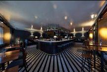 HOSPITALITY: Paisano Bar München / Eine Bar, wie sie in New York, London oder Istanbul liegen könnte, mit prominentem Inhaber, coolem Namen und exquisitem Interieur. Und, mit der perfekten Beleuchtung! Die Rede ist von der kürzlich von Schauspieler Elyas M'Barek in München eröffneten Paisano Bar. lui Strahler zaubern auf der Mahagonivertäfelung honigfarbenes Licht, das sich im Marmorboden spiegelt, Sento verticale mit Lichtwirkung E auf anthrazitfarbener Wand erzeugen spannende Schattenspiele.