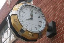 Bracket Clocks / A double-sided clock mounted perpendicular to a wall (or pedestal) or mounted to a post, to be seen from two directions. All of our clocks are built-to-order, as each application is different.  www.lumichron.com