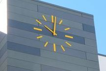 Skeletal (Silhouette) Clocks / A clock with numbers and hands only, mounted on a wall. No self-contained illumination. A background dial is optional. The clock movement is behind the wall and is built to hold appropriately sized hands. As the clock hands are exposed, they are made to withstand extreme weather conditions and are fastened to the shafts with set screws. Once fastened, time adjustments are only possible by activating the movement motors. All of our clocks are built-to-order.  www.lumichron.com