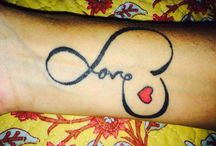 """Tattoos / The Tattoo on my wrist say s """"Love"""" with a red    ❤️cause I am a Love-BUG & the heart shaped ladybug behind my Ear. & others. They all have super special meanings to me. My back has my family flower vine ( pic uploaded)  / by BUG 🐞"""