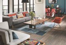 ambiance neutre avec un brin de peps / - un sol beige foncé, peut-être imitation bois - murs clairs dans la continuité de la nuance du sol ou en couleur complémentaire toujours clairs - canapé en cuir noir  - un pan de couleur  - des plantes vertes  - une touche de couleur vive : meubles, déco ?