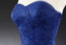 Jean Dessès (French, born Eqypt, 1904–1970) / Jean Dessés opened his own couture house in Paris in 1937 and became known for his characteristic twists and gathers which he magically executed on a variety of fabrics. Considered his best work are his evening dresses of chiffon, which have the appearance of classical sculpture. He favored ombré fabrics and colors other than black, such as Wedgwood blue, old rose, taupe, eggplant, green, brown, pale grays, faint pinks, and whites.
