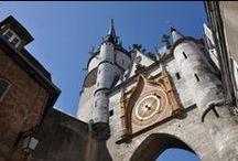 Tour de l'Horloge / Construite au XVème siècle, la Tour de l'Horloge marque le cœur du secteur piétonnier. Appuyée à la Tour, une chambre contient le mécanisme de l'Horloge installée par les bourgeois d'Auxerre au XVe siècle. La particularité de l'Horloge provient de ses deux aiguilles. Distinctes l'une de l'autre par le soleil ou la lune visibles à leur extrémité, elles indiquent les mouvements solaires ou lunaires.