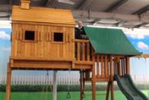 Fantasy Tree House Swing Sets / The Fantasy Tree Swing Set is amazing! Remember when you were young and had your own tree house? That place you could call your own! Now you don't have to build one for your kids, we've done the work for you! Our Fantasy Tree House #1 starts with the 5' clubhouse with a 10' wave slide and steel rung access ladder. Our exclusive bridge connector to a 7' high Tree House incorporates double-wide monkey bars underneath the tree house and bridge connector!