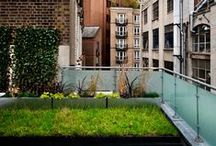 BARBICAN - Urban Roof Gardens / BARBICAN: This office roof terrace originally looked very unwelcoming and bare. We replaced the original steel balustrade with frosted glass and installed decking, which we stained. We added some much needed greenery to this industrial space by planting some planters with a green wall, grasses and a selection of small trees. Our client now has a wonderful space to meet his clients in!
