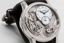 Romain Gauthier Logical One Secret and Logical One / Logical One features a triple patent-pending Romain Gauthier flat chain-and-fusee style constant force system with ruby chain links, ergonomic push button winding system, dial-side visible balance, mainspring barrel with sapphire inserts, plus a 60-hour power reserve indicator.