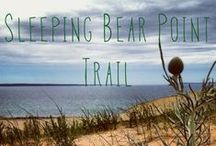 Sleeping Bear Point Trail / The #9 trail on our maps and in our trail guide is considered a strenuous 2.8 mile hike. The trail is hilly, all sand, and no shade which leads hikers onto the dunes, through a ghost forest, and over looks Lake Michigan. Blue tipped posts mark the trail. Plan ahead. Take water, sunscreen, shoes, hat and a snack. Trailhead is located at the end of Sleeping Bear Dunes Rd., west of the maritime Museum. / by Sleeping Bear Dunes National Lakeshore