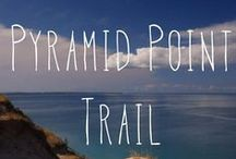 Pyramid Point Trail / #12 on our map and in our trail guide, Pyramid Point is a 1.2-2.7 mi round trip moderate hike. This hilly tails goes through beach-maple forests and Fields to a high outlook over Lake MI.  For your safety and to prevent erosion, please do not descend the bluff. Trailhead: off Basch Rd, follow Port Oneida Rd. north from M-22 / by Sleeping Bear Dunes National Lakeshore
