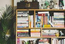 ein heim / bokhyller fulle av bøker og støv, koppar i alle fargar, planter på golvet og i alle vindaugskarmar.