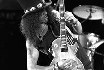 Slash / Saul Hudson (born July 23, 1965), better known by his stage name Slash, is a British musician and songwriter.He is best known as the former lead guitarist of the American hard rock band Guns N' Roses, with whom he achieved worldwide success in the late 1980s and early 1990s. During his later years with Guns N' Roses, Slash formed the side project Slash's Snakepit. He then co-founded the supergroup Velvet Revolver, which re-established him as a mainstream performer in the mid to late 2000s.