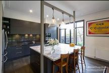 Malvern East Kitchen, Lounge & Bathroom / Designer: Maree Howley of Beautiful Room with Daniel Spargo Location: Malvern East Photography by Yvonne Menegol The beautiful big windows allow the light to flood in, meaning the dark kitchen cabinetry work perfectly and aren't too heavy for the space. Adding in the matching buffets and floating shelves into the lounge room helps the two spaces tie together in their semi-industrial meets eclectic feel.