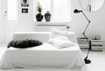 Wohnzimmer / Living Room / Wohnzimmer à la hell und nordisch - geradlinige Sofas, grafische Teppiche und schlichte Regale in Schwarz, Weiß und Naturtönen vermitteln warmen Minimalismus.