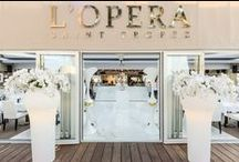 » L'Opera Saint Tropez Restaurant | Cote D'Azur | France « / L'Opera is a unique experience in the heart of the Saint-Tropez village. The ultra-chic, white and gold décor throughout emphasizes the designs and refinement in keeping with the area without any ostentation. VG lighting, vases and flower arrangements were chosen to be part of this elegant atmosphere.
