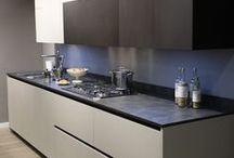 CUCINA LOGICA di VALDESIGN / La perfezione e l'eleganza di una cucina dallo stile minimal. I #Pensili sulla parte alta del piano cottura sono di profondità maggiorata e colonne in finitura 3D Concrete Lava.  Il TOP è in finitura Caesar Brown spessore 2cm Gole, zoccoli e dettagli in metallo colore moka shine. Lavello by @Barazza filo top.  PIANO COTTURA by Smeg Italia in Acciaio Inox con griglia in ghisa e cappa integrata. Tutti i ripiani della dispensa libreria e i cassetti interni sono in impiallacciato olmo biscotto.